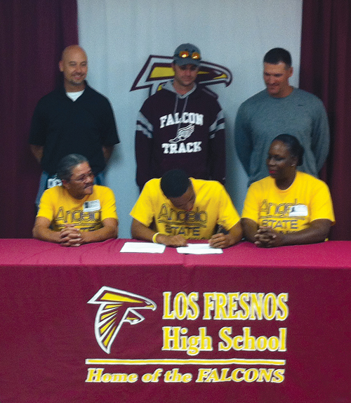 Akeem signs as his parents, coaches Shawn Jones, Will Littleton and Director of Athletics Clint Finley, look on