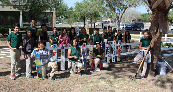 7th & 8th-grade science teacher Mr. Christopher Martinez poses with his Garden Club students in front of their colorful garden.