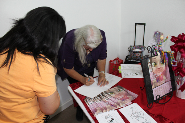 Author Sylvia Weaver Rivera signs copies of her book Sarah and the Little Spider Prince during a Meet and Greet at Hopes & Dreams Collectibles. Photo: Victor Moreno/LFN