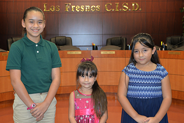 Leading the Pledge of Allegiance at the start of the meeting were students whose parents work at the District Service Center. In the photo are (left to right) Mia Hernandez, Resaca Middle School; and sisters Aime and Madeleine Chavez, both at Lopez-Riggins Elementary School.