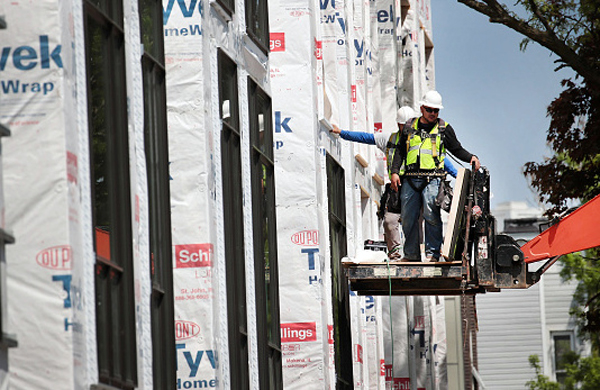 Construction workers put the finishing touches on new townhouses in Dallas. The high cost of housing is making it difficult for low-income Texans to find an affordable home. Photo: ScottOlson/Getty Images