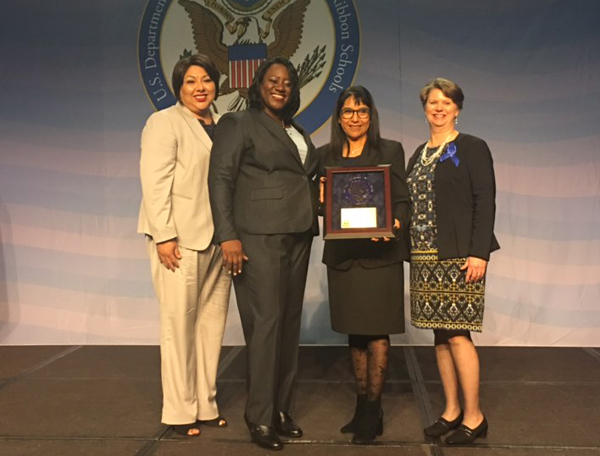 Maria Elisa Pineda holds National Blue Ribbon Award plaque presented last Tuesday, November 7th.
