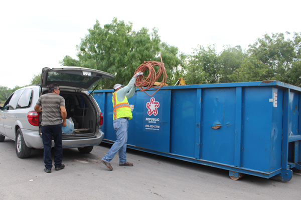 Benito Torres, left, takes junk out of his vehicle as Lupe Alvarado, an employee with the city's public works department, throws an old hose into a trash bin parked at the end of the street