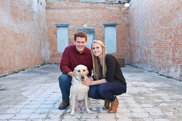 Scott and Hillary Oswald pose for an engagement photo with Alika, Hillary's guide dog.