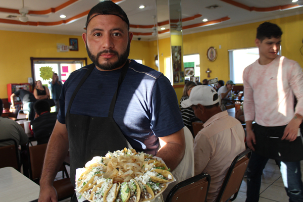 Jose Luis Torres shows a crown of taquitos prepared at the eatery in Los Fresnos.