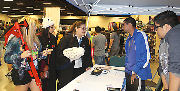 Julianne Gaytan and Ale Garza, students at La Feria Emergency Education Training Center, talk to a couple Comic Con fans.