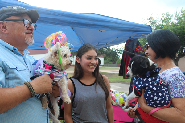 Los Fresnos resident Juan Vasquez, left, holds Chloe, while Jessica Villarreal looks at the pooch named Keilan Juan's wife Ida is holding. Photo: Tony Vindell/LFN