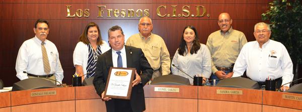 Superintendent Dr. Gonzalo Salazar receives plaque for achievement of doctoral degree.