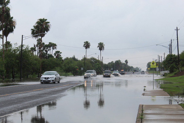 Vehicles going cautiously last Thursday along North Arroyo Boulevard as resaca waters went over the road.
